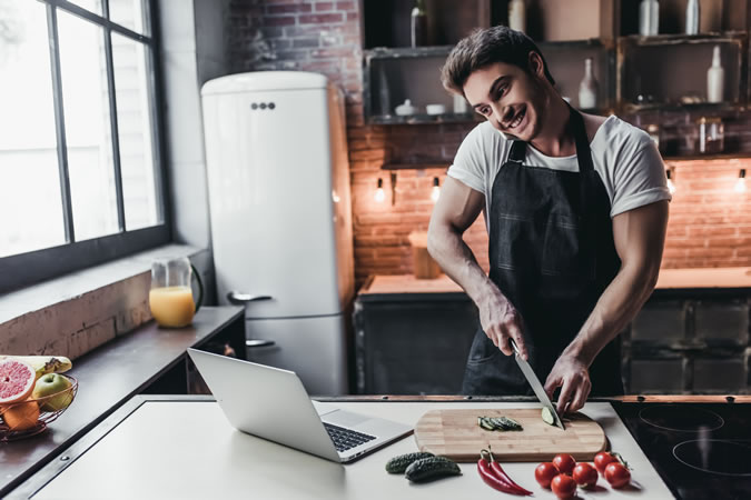 Man Cooking And Looking At A Laptop